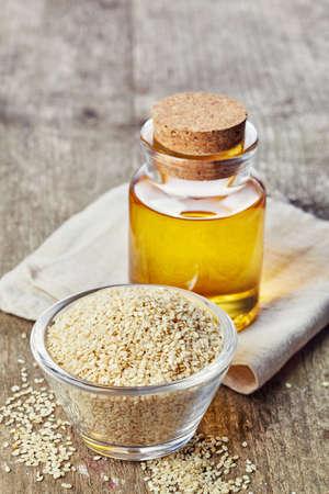 ajonjoli: Botella de aceite de semilla de sésamo y plato de semillas de sésamo en el fondo de madera