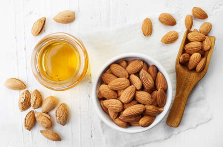 almond: Almond oil and bowl of almonds on white wooden background. Top view