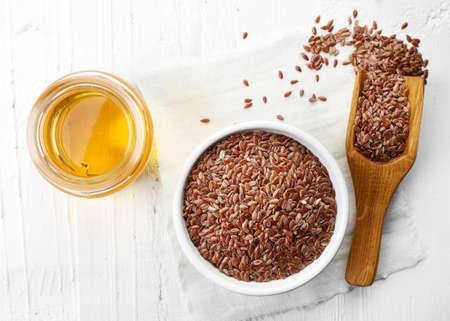 organic flax seed: Linseed oil and bowl of linseeds on white wooden background. Top view