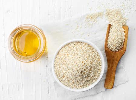 olio di semi di sesamo e ciotola di semi di sesamo su sfondo bianco in legno. Vista dall'alto