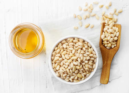pine nut: Pine nut oil and bowl of pine nuts on white wooden background. Top view Stock Photo