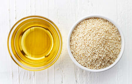 Sesame seed oil and bowl of sesame seeds on white wooden background. Top view Stock Photo