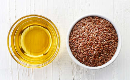 flax seed oil: Linseed oil and bowl of linseeds on white wooden background. Top view