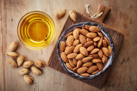 Almond oil and bowl of almonds on wooden background. Top view