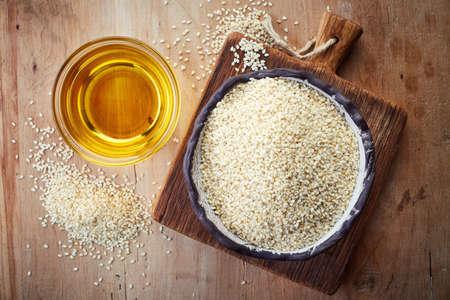 ajonjoli: aceite de semilla de sésamo y plato de semillas de sésamo en el fondo de madera. Vista superior Foto de archivo