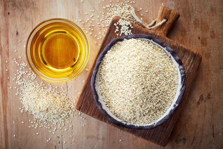 Sesame seed oil and bowl of sesame seeds on wooden background. Top view