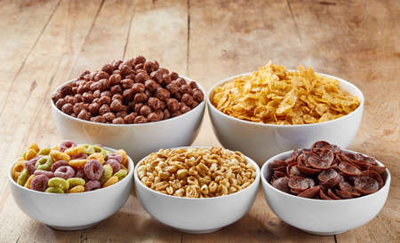 Bowls of various cereals on wooden background