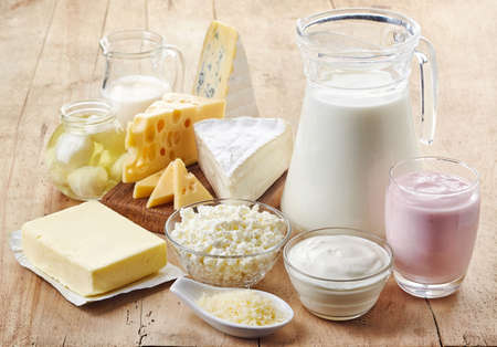 Various fresh dairy products on wooden background Standard-Bild