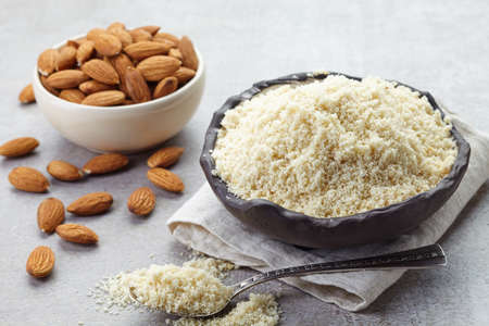 Bowl of almond flour and bowl of almonds