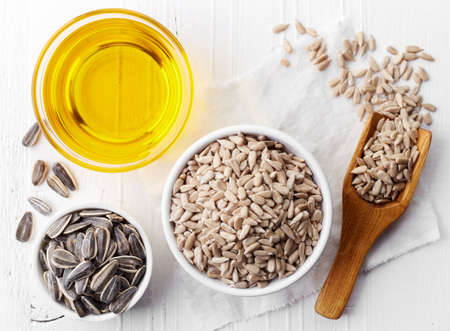 Bowl of sunflower seeds and bowl of sunflower oil on white wooden background. Top view