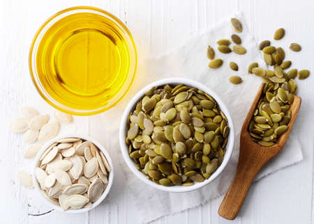 Bowl of pumpkin seed oil and pumpkin seeds on white wooden background. Top view