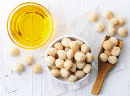 Bowl of macadamia nut oil and macadamia nuts on white wooden background. Top view 写真素材