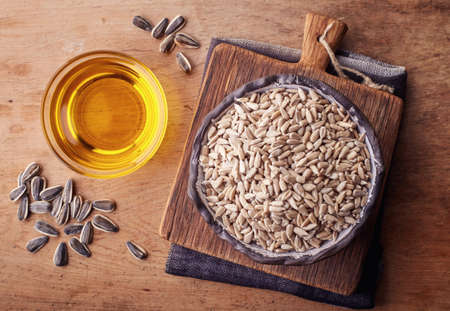 Bowl of sunflower oil and sunflower seeds on wooden background. Top view