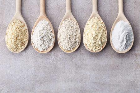 상위 뷰에서 다양한 글루텐 무료 밀가루 (아몬드 가루, 아마란스 씨앗 가루, 메밀 가루, 쌀가루, 병아리 완두콩 가루)의 나무 숟가락