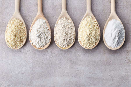 Wooden spoons of various gluten free flour (almond flour, amaranth seeds flour, buckwheat flour, rice flour, chick peas flour) from top view Foto de archivo