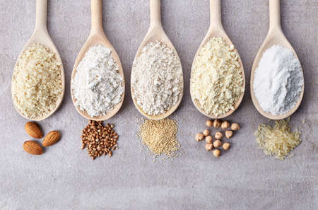 Wooden spoons of various gluten free flour (almond flour, amaranth seeds flour, buckwheat flour, rice flour, chick peas flour) from top view Stockfoto