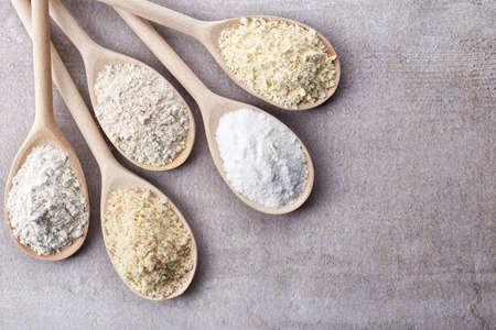 seeds of various: Wooden spoons of various gluten free flour (almond flour, amaranth seeds flour, buckwheat flour, rice flour, chick peas flour) from top view Stock Photo