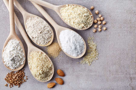 Wooden spoons of various gluten free flour (almond flour, amaranth seeds flour, buckwheat flour, rice flour, chick peas flour) from top view Stock Photo