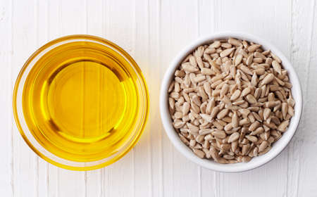 Sunflower oil and sunflower seeds on white wooden background from top view
