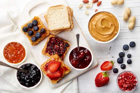 mantequilla: Emparedados con mantequilla de maní, mermelada y frutas frescas en el fondo blanco de madera de la visión superior Foto de archivo