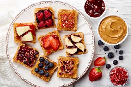 Plaat van broodjes met pindakaas, jam en verse vruchten op witte houten achtergrond van hoogste mening Stockfoto