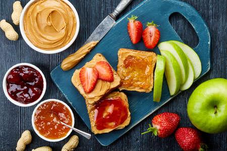 mermelada: Sandwiches con mantequilla de maní, mermelada y frutas frescas en el fondo de madera oscura de la visión superior