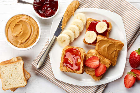 peanut butter and jelly sandwich: Plate of sandwiches with peanut butter, jam and fresh fruits from top view Stock Photo