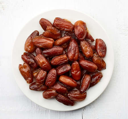 White plate of dried dates on white wooden background. From top view
