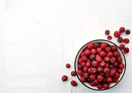 Bowl of dried cranberries on white wooden background with space for text. From top view Banco de Imagens