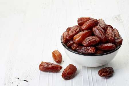 Bowl of dried dates on white wooden background