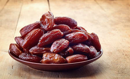 dried: Plate of dried dates on wooden background