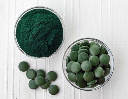 spirulina: Spirulina algae powder and tablets on white wooden background from top view