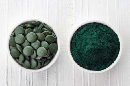 algae: Spirulina algae powder and tablets on white wooden background from top view