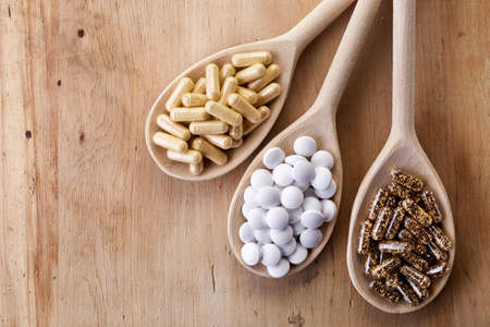 Wooden spoons of various dietary supplements on wooden background