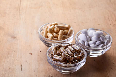 dietary supplements: Bowls of various dietary supplements on wooden background