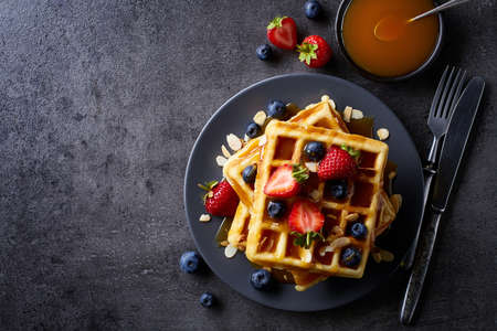 Plate of belgian waffles with caramel sauce and strawberries on dark gray background. From top view