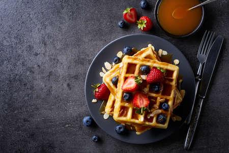 Placa de waffles belgas con salsa de caramelo y fresas sobre fondo gris oscuro. Desde la vista superior