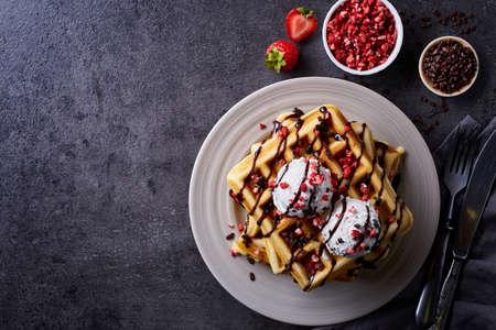 벨기에 와플 어두운 회색 배경에 초콜릿 소스와 아이스크림 접시. 위에서 본 모습