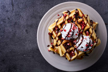 Plate of belgian waffles with chocolate sauce and ice cream on dark gray background. From top view Standard-Bild