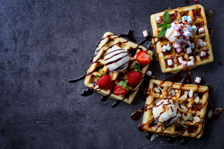 Three various belgian waffles on dark wooden background. From top view Imagens - 61039714