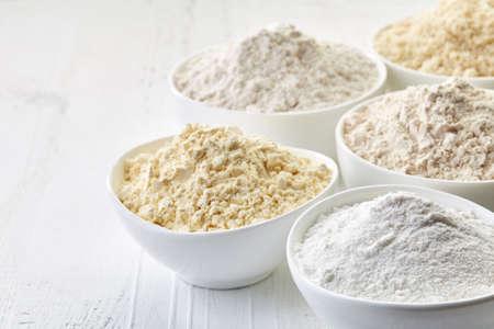 Ciotole di varie farine senza glutine (ceci, riso, grano saraceno, semi di amaranto, mandorle) su sfondo bianco in legno Archivio Fotografico