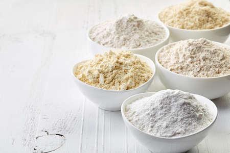 Miseczki różnych mąki bezglutenowej (groch, ryż, gryka, nasiona amarantusa, migdały) na białym tle drewnianych