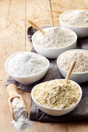 Bowls of various gluten free flour (chick peas, rice, buckwheat, amaranth seeds, almond) on wooden background Stockfoto