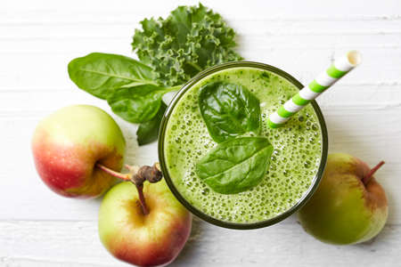 Glass of green fruit and vegetable smoothie on white wooden background from top view