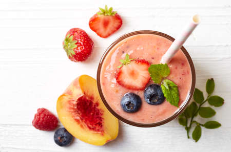 Glass of fruit and berry smoothie on white wooden background from top view