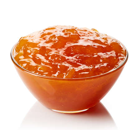 Bowl of apricot jam isolated on white background