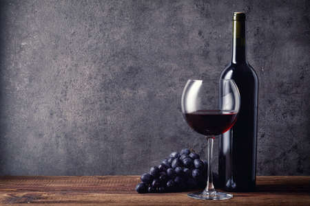 sulphide: Bottle and glass of red wine and grapes on dark background