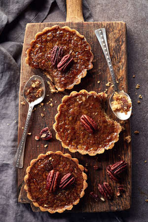 pecan pie: Homemade mapple syrup and pecan tarts on wooden cutting board from top view Foto de archivo