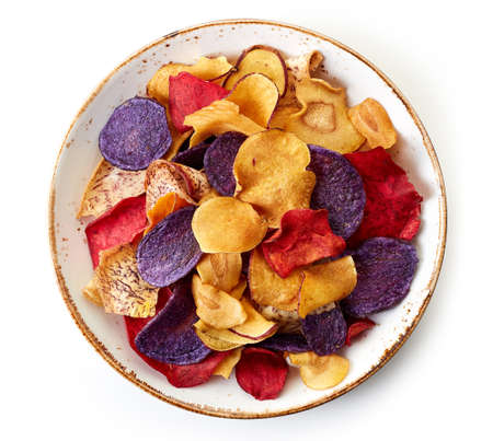 Bowl of healthy colorful vegetable chips isolated on white background from top view