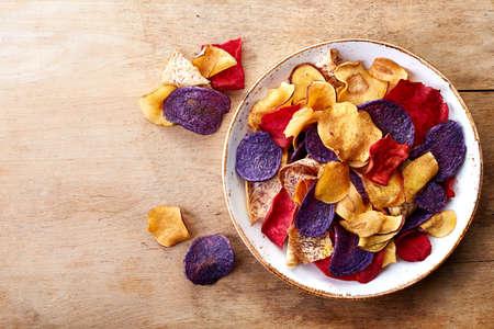 batata: Tazón de sanas chips de verduras de colores sobre fondo de madera de la visión superior